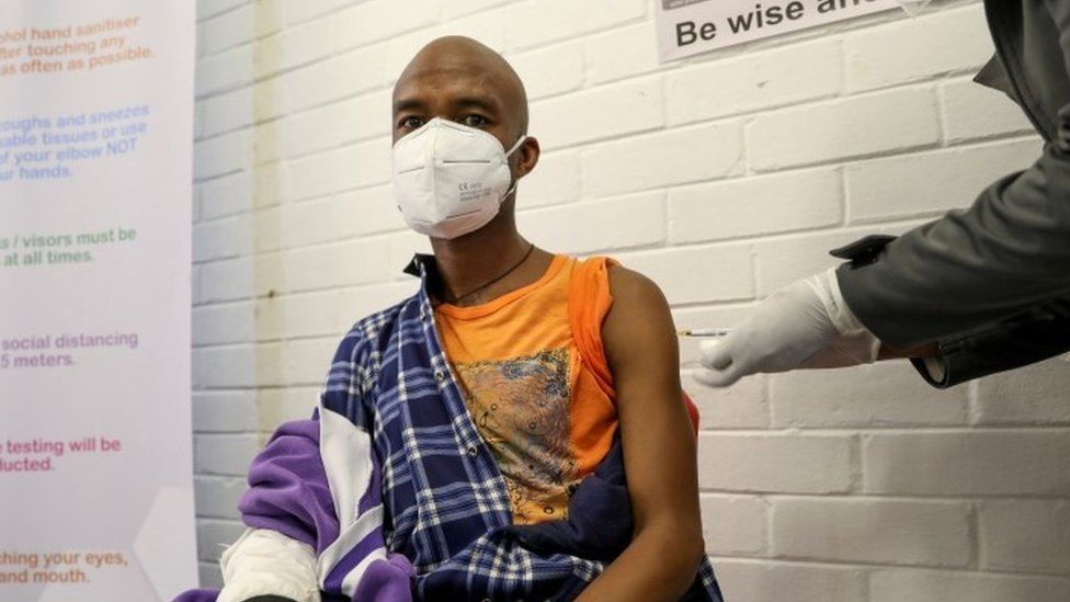 A South African man is given a dose of an experimental vaccine