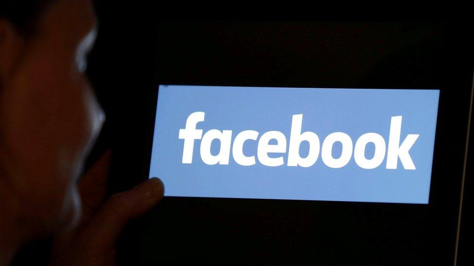 امرأة تنظر إلى شعار فيسبوك على جهاز آيباد في هذه الصورة التوضيحية التي تم التقاطها في 3 يونيو/حزيران 2018