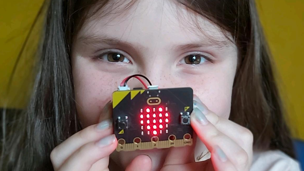 A young girl holds the Micro Bit