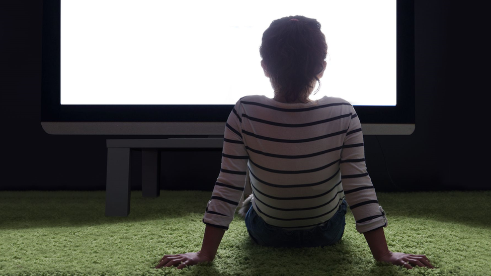 Child staring at a huge screen