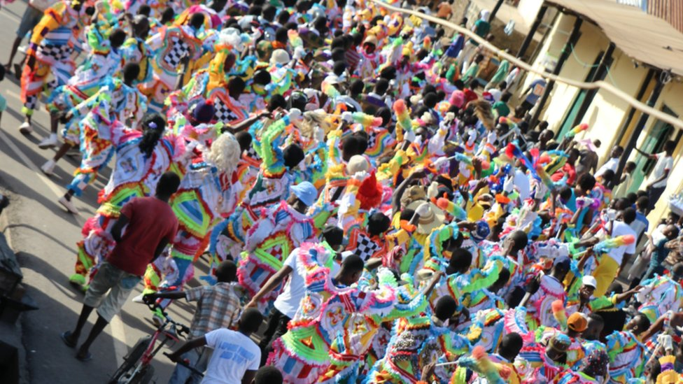 large groups dressed in multi-coloured costumes parade through the city centre in Sekondi Ghana