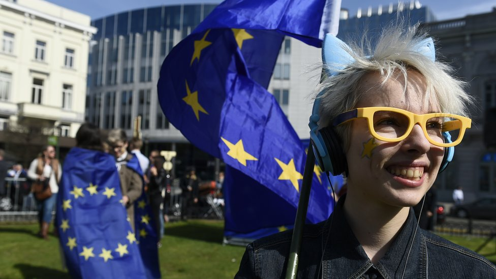 A woman with yellow glasses and a star painted on her cheek smiles and carries the EU flag outside the EU Parliament in Brussels