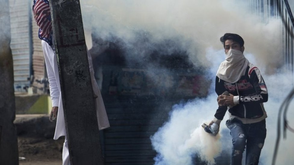 A Kashmiri Muslim protester prepares to throw back a tear gas canister at Indian security personnel as another takes cover behind an electric pole during a protest after Eid al-Adha prayers in Srinagar, Indian controlled Kashmir, Tuesday, Sept. 13, 2016