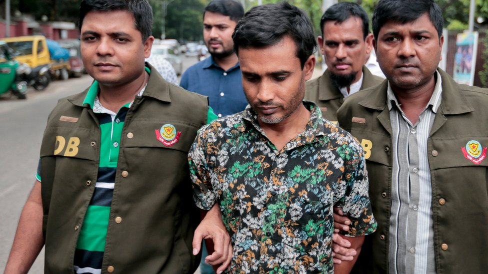 Members of Bangladesh Police Detective Branch (DB) escort a man, centre, whom they have identified as Shariful Islam Shihab, a former member of the banned Islamic group Harkatul Jihad as they walk him in front of the media in Dhaka, Bangladesh, Sunday, May 15,
