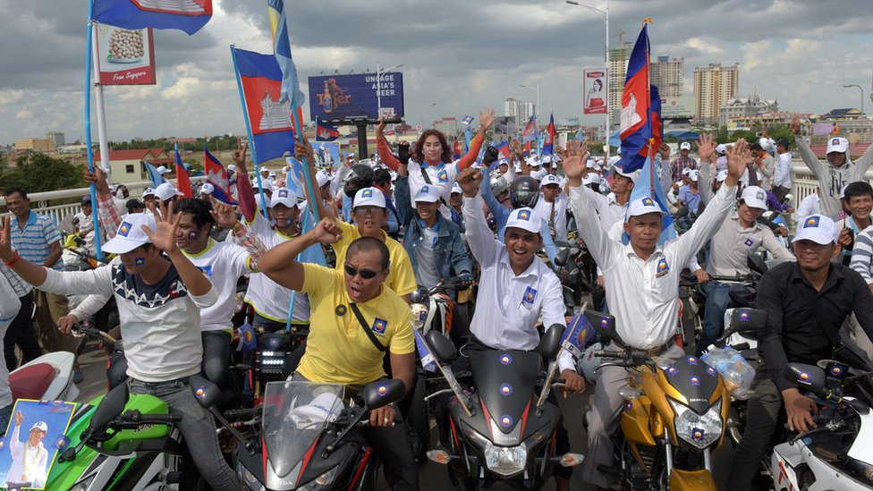 CNRP supporters cheering with flags during a rally