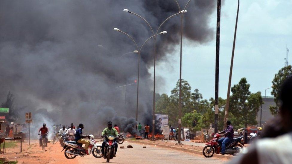 Residents burn tyres along a street in Ouagadougou on September 17, 2015