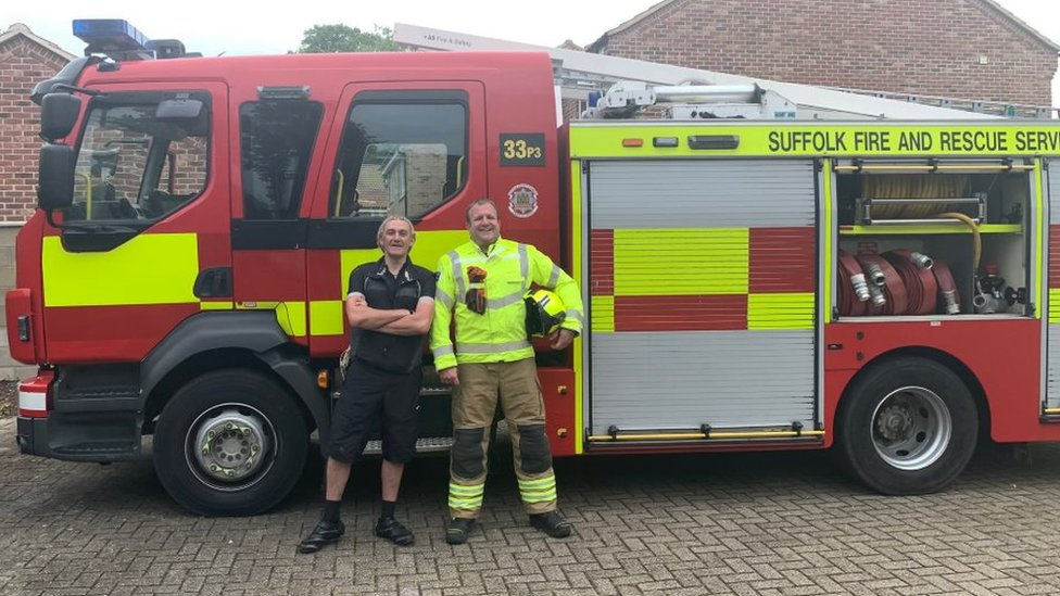 Paul and a firefighter in front of a fire engine in Suffolk