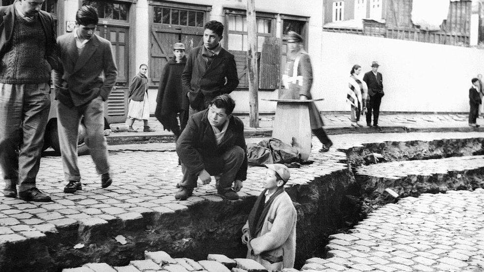 Un joven en una de las grietas en la calle producto del terremoto en Valdivia, Chile, en 1960.