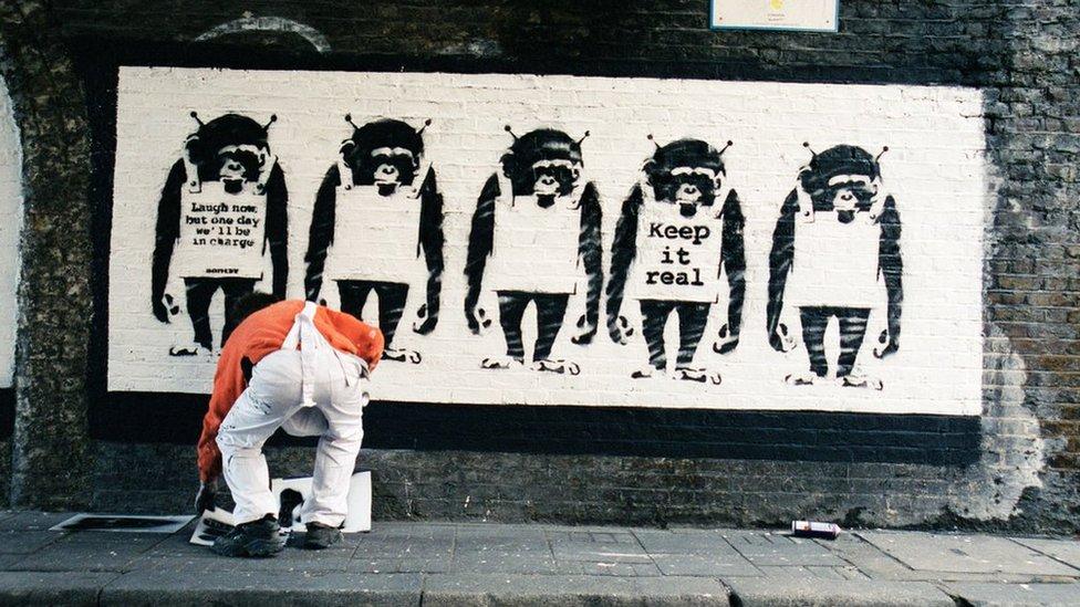 Artist by a Banksy artwork
