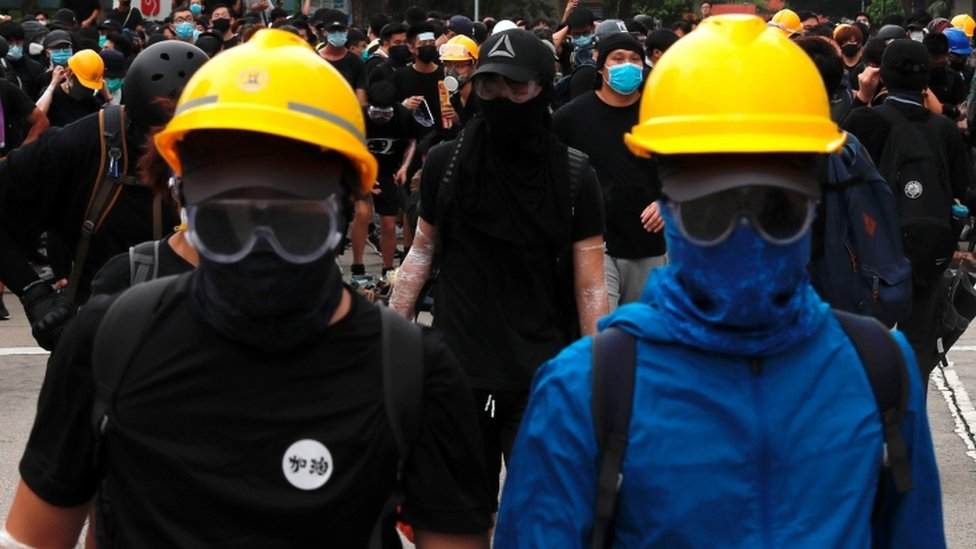 Two protesters wear yellow hard hats during protests in Hong Kong