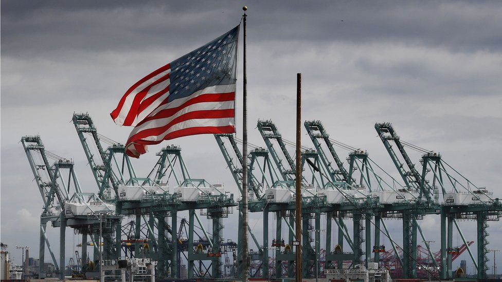 The US flag flies over shipping cranes and containers after a report said the United States and China are close to reaching a major trade deal that would see both sides lower some of the tariffs imposed during an often-bitter trade war, in Long Beach, California on March 4, 2019.