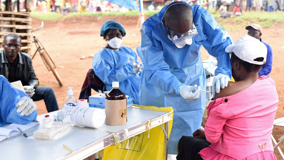 A Congolese health worker administers Ebola vaccine to a woman who had contact with an Ebola sufferer in the village of Mangina in North Kivu
