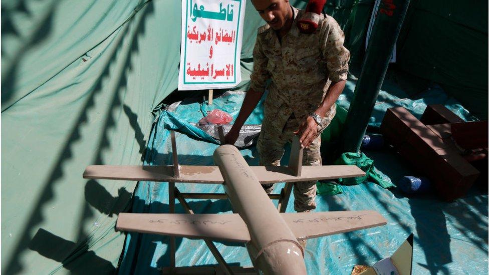 جندي حوثي يتفقد نماذج صواريخ وطائرات بدون طيار.