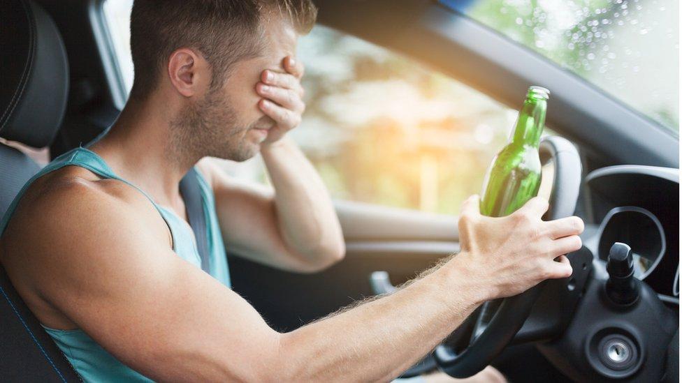 Hombre al volante con una botella en la mano