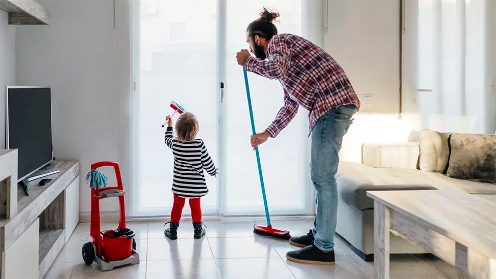 Un hombre y su hij@ limpian la casa