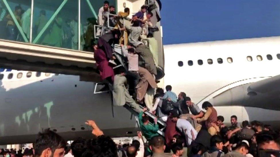 Civiles afganos intentan desesperadamente subir a un avión en el aeropuerto de Kabul