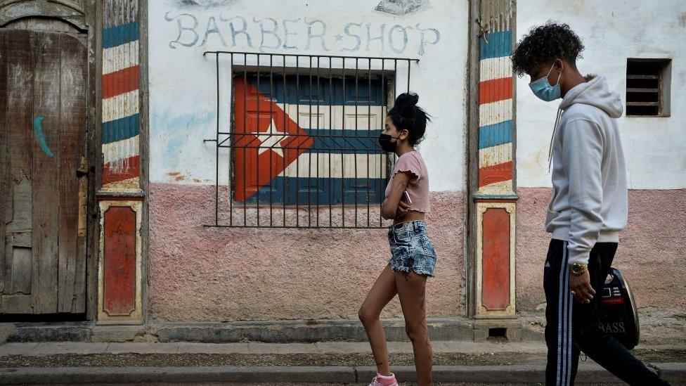 Dos personas caminando en una calle cubana.