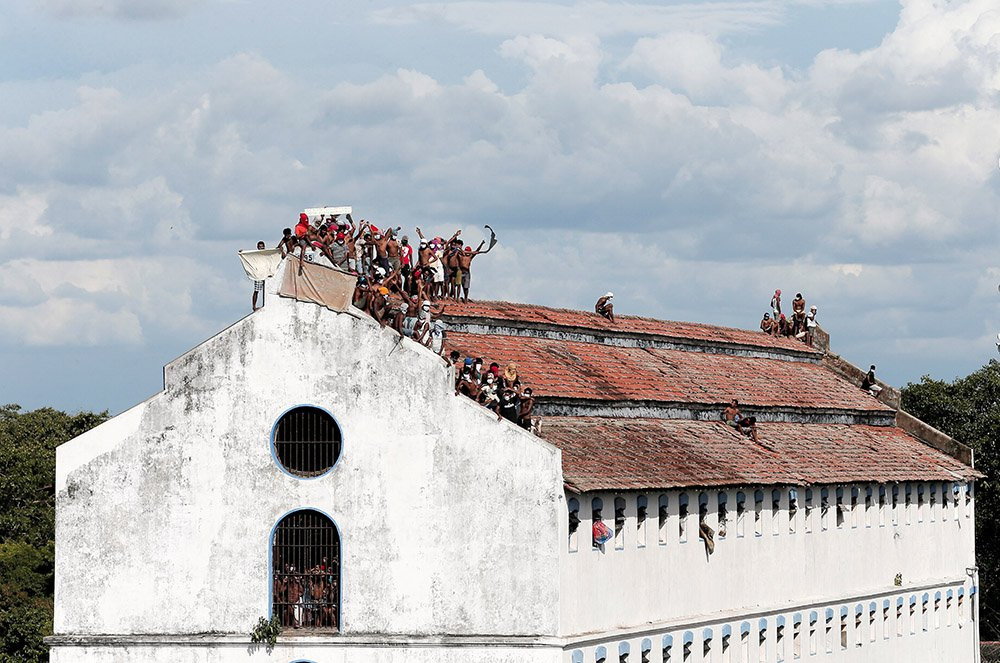 Inmates protest on the top of a prison building
