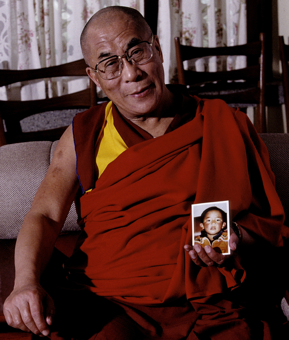 The Dalai Lama holding the only known photograph of the Panchen Lama