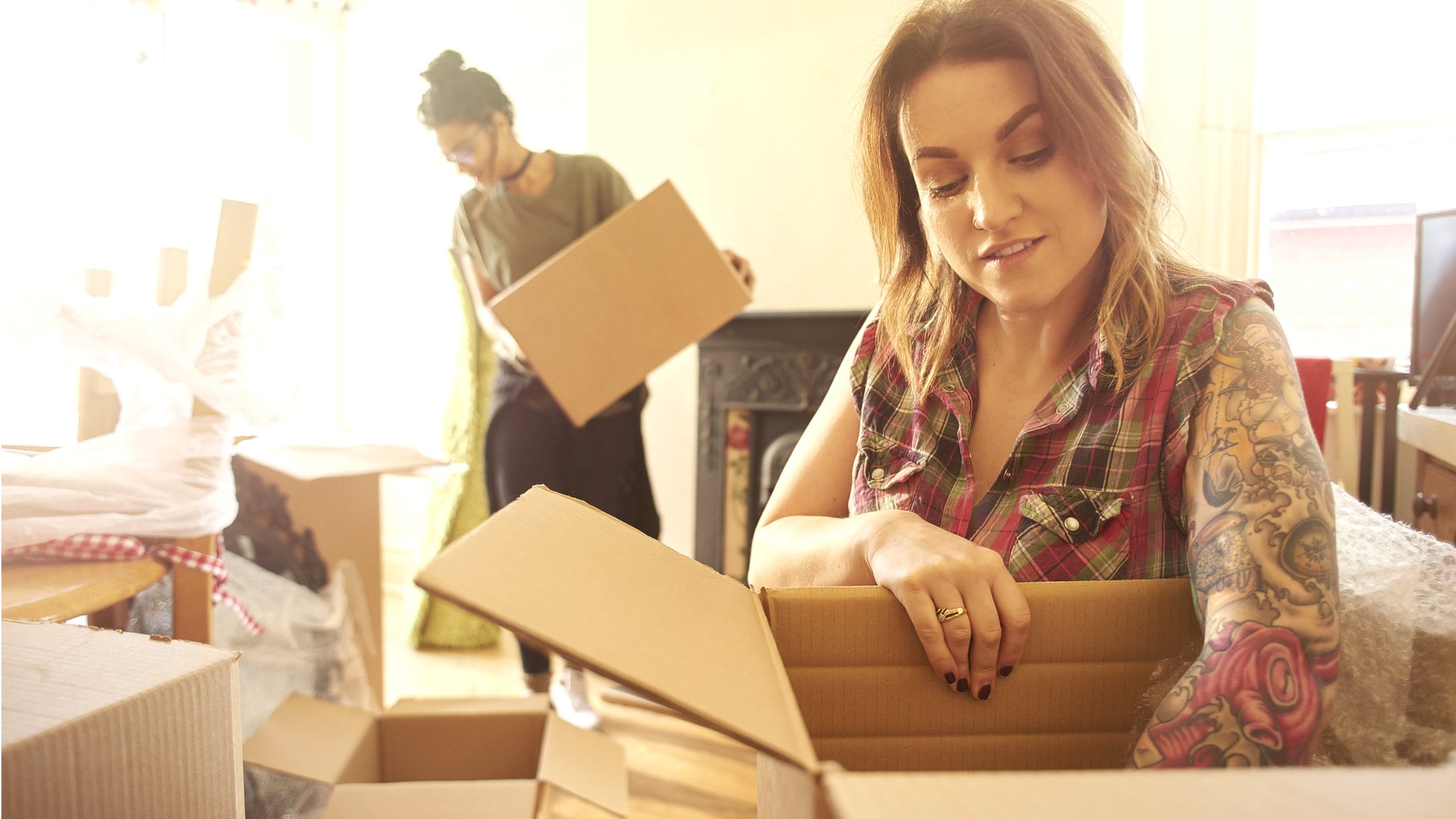 Young woman packing a box as she moves house