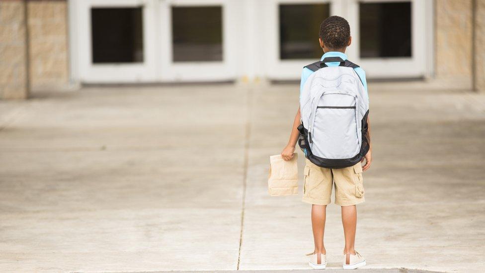 Niño con una mochila de espaldas.