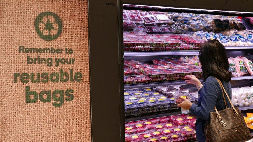 Mujer en supermercado con cartel que recuerda usas bolsas reutilizables.