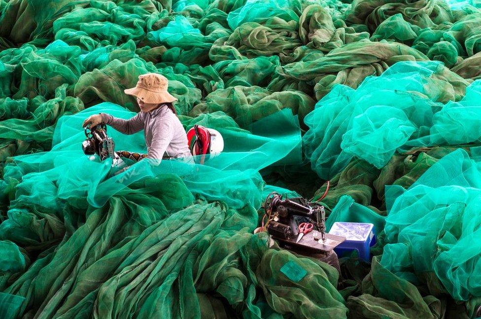 A woman repairs fishing nets