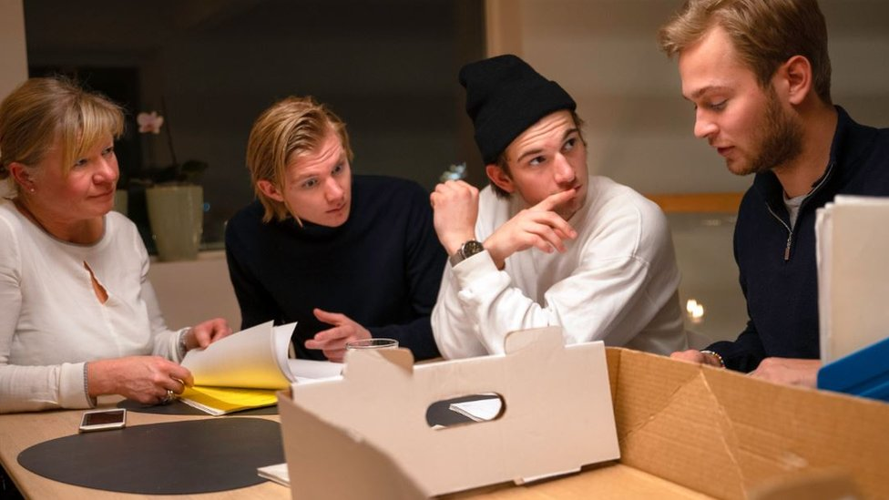 The members of the crime club sit around a table with boxes and papers on