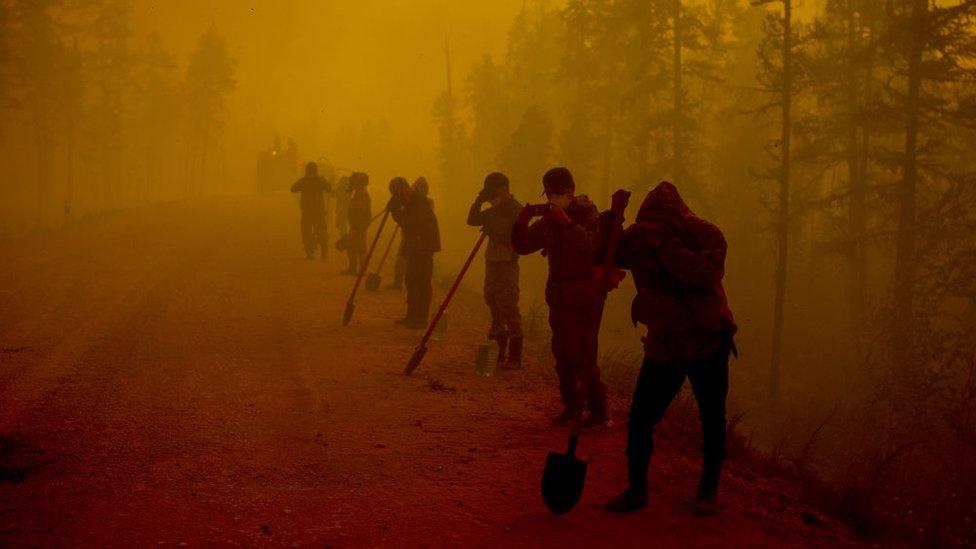 Trabajadores se cubren ante el humo por los incendios en Yakutsk, Rusia.