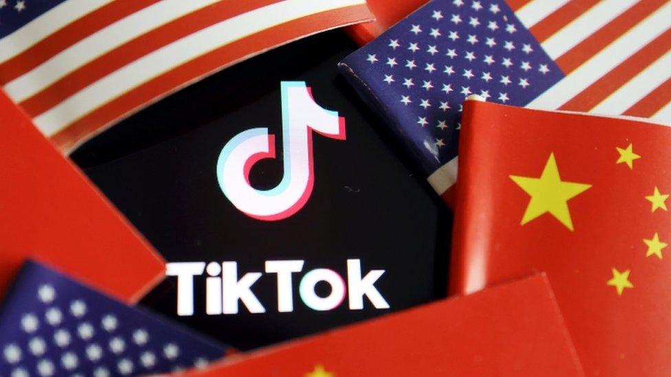 Banderas china y estadounidense alrededor del logo de TikTok.
