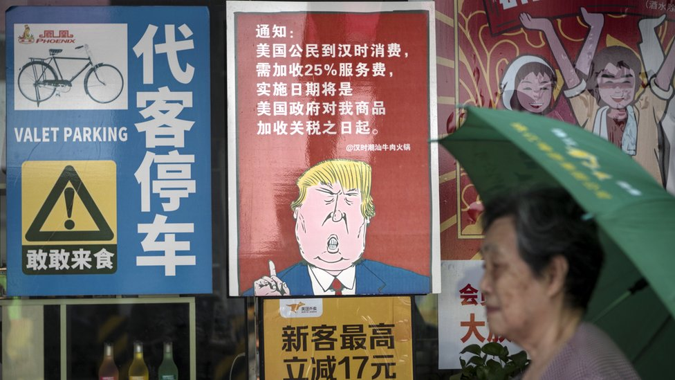A woman passes by a restaurant with a poster depicting US President Donald J. Trump, stating that, in Guangzhou, Guangdong Province, China, 13 August 2018.