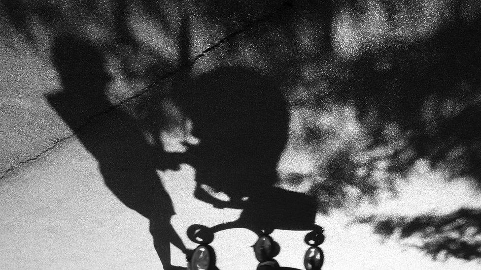 La sombra de una mujer empujando un coche de bebés.