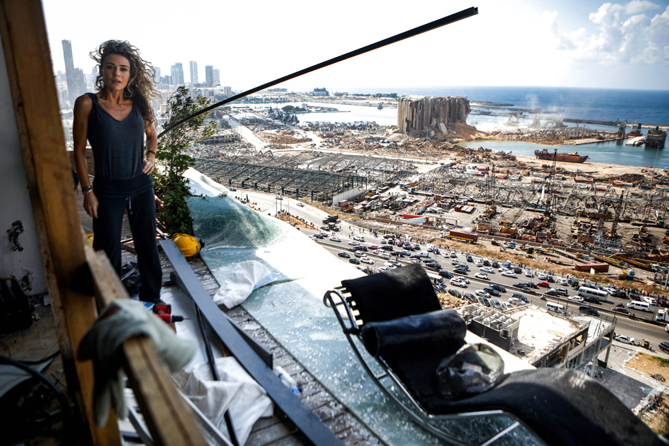 Karina Sukkar stands on the balcony of her damaged apartment overlooking the ravaged port of Beirut