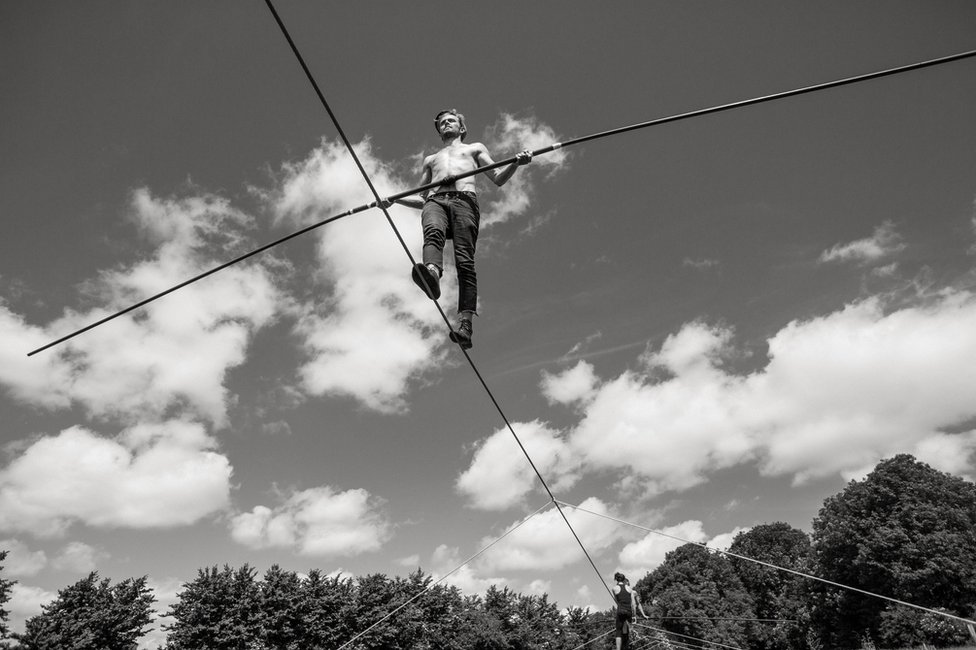 A man walks along a tightrope holding a large pole