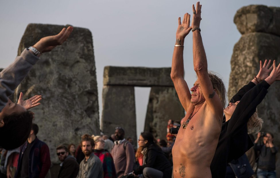 Revellers practice yoga as the sun rises and = they celebrate the pagan festival of Summer Solstice at Stonehenge in Wiltshire, southern England on June 21, 2017.