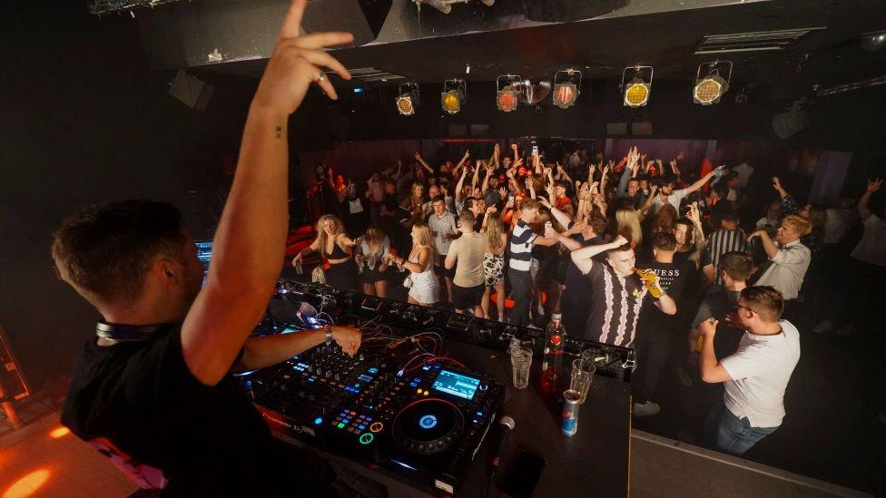 DJ frente a jóvenes bailando en un club nocturno en Londres.