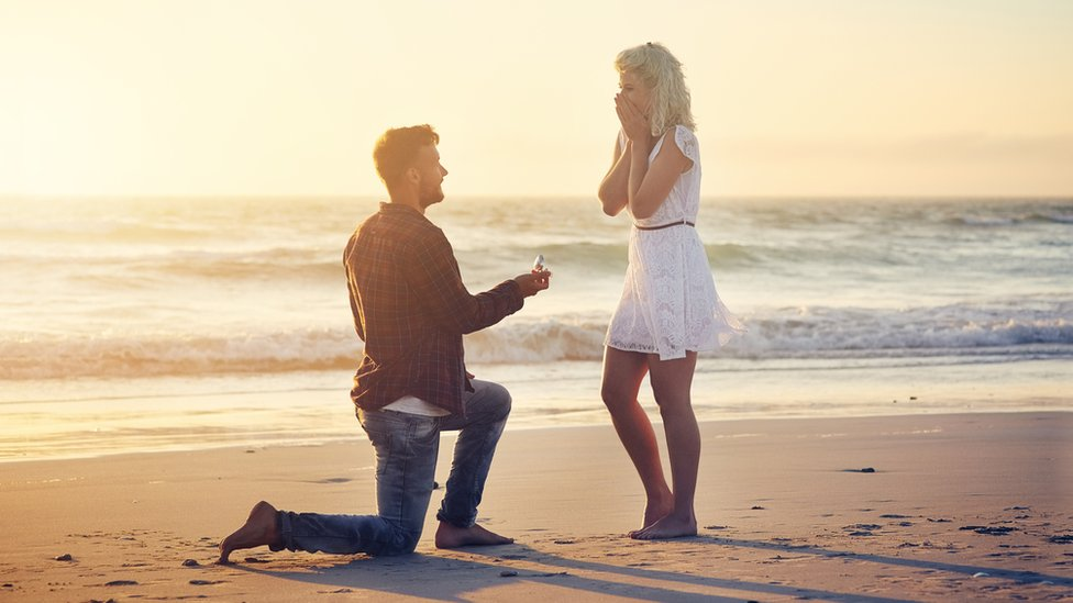Un hombre pidiéndole matrimonio a una mujer en la playa
