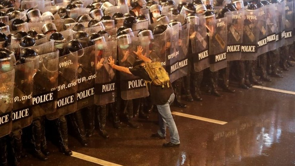 A man pushes against riot police officers in Bangkok, Thailand. Photo: 16 October 2020