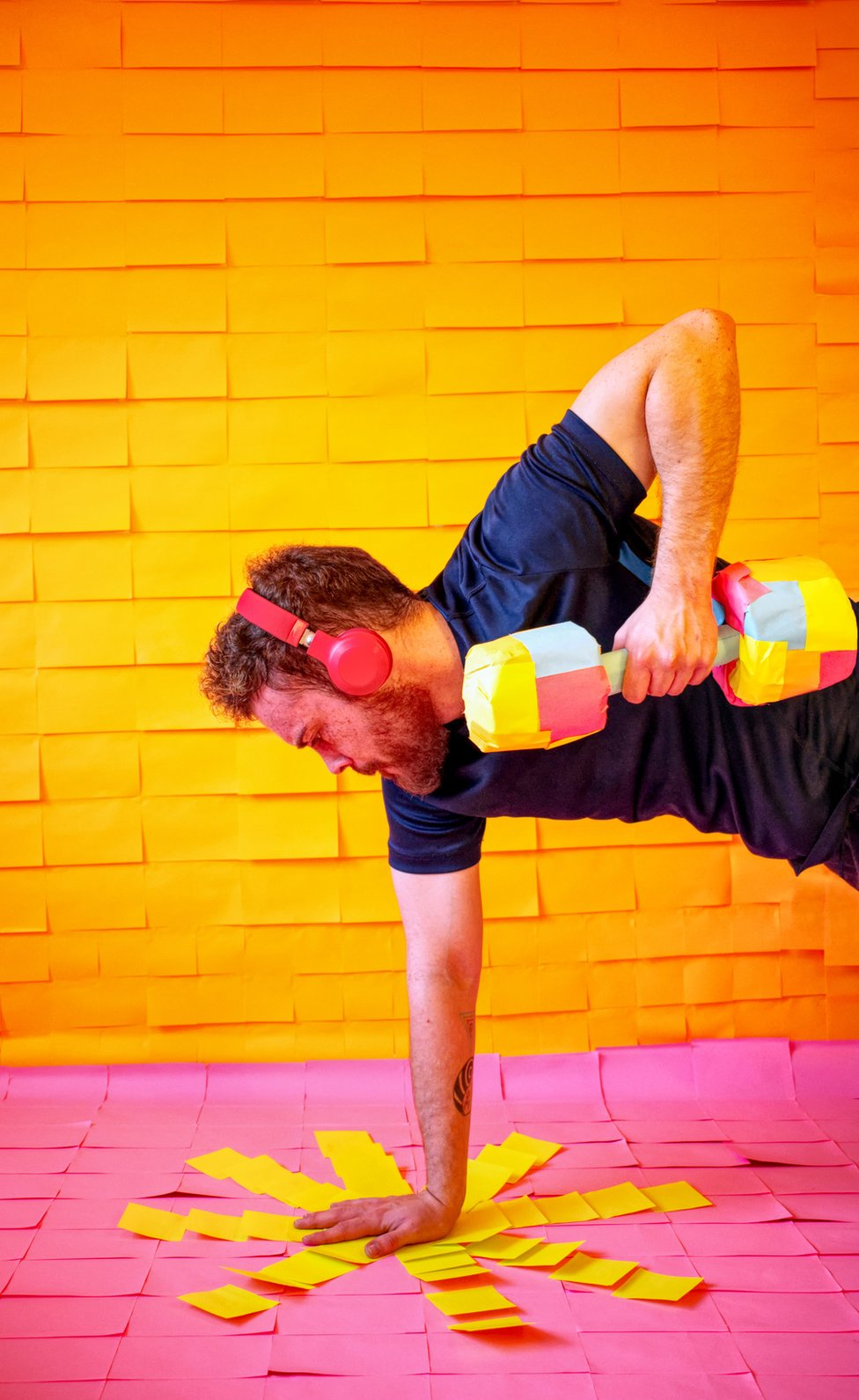 A man exercises surrounded by colourful post-it-notes