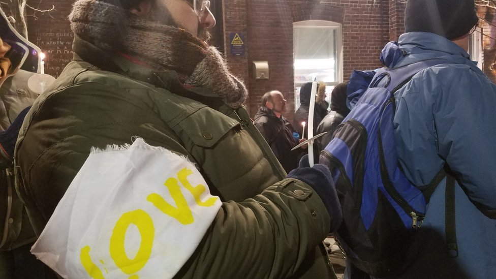 """An attendee at the vigil wears an armband with the word """"love"""""""