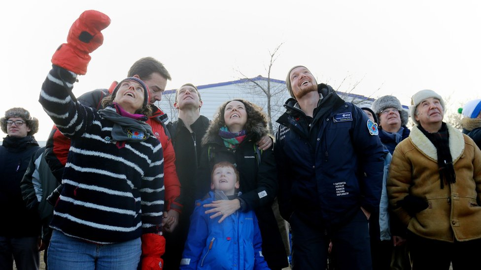 Tim Peake's wife Rebecca (centre, their son Thomas and others look up, watching the launch of a spacecraft in Kazakhstan.
