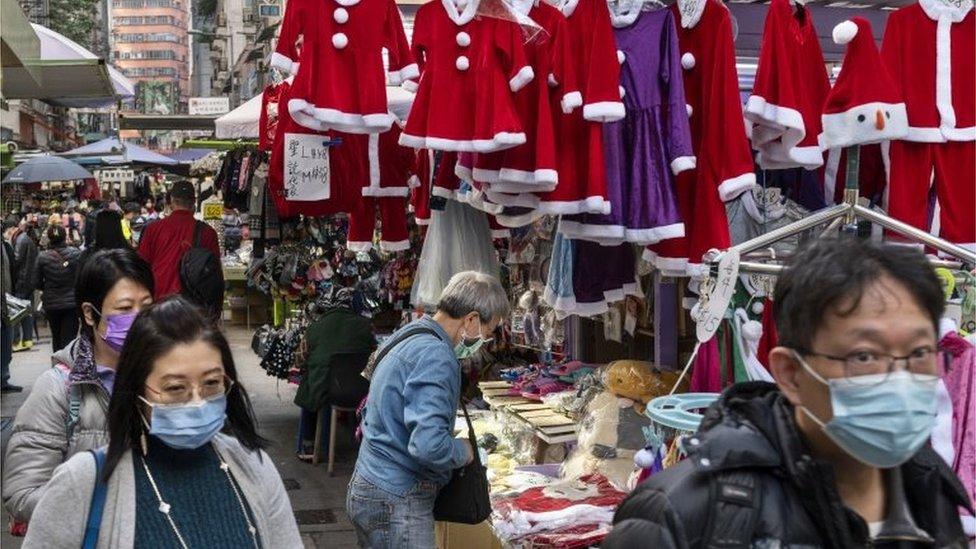 Pedestrians walk past a Christmas costume street shop in Hong Kong, China, 21 December 2020.