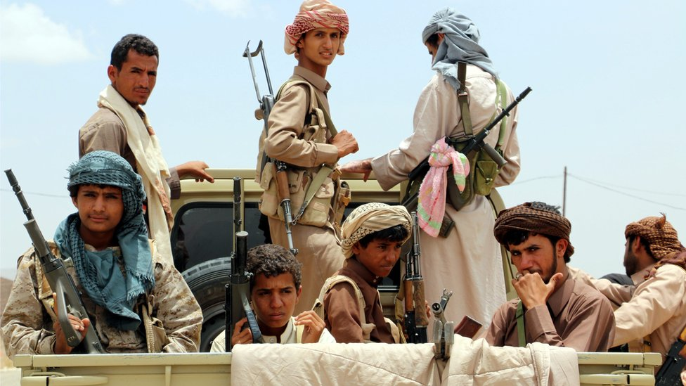 Yemeni fighters ride on a vehicle during an offensive against Houthi rebels positions