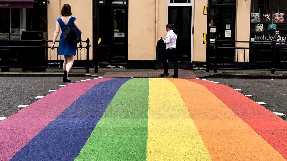 People on a LGBTQ rainbow street crossing in London