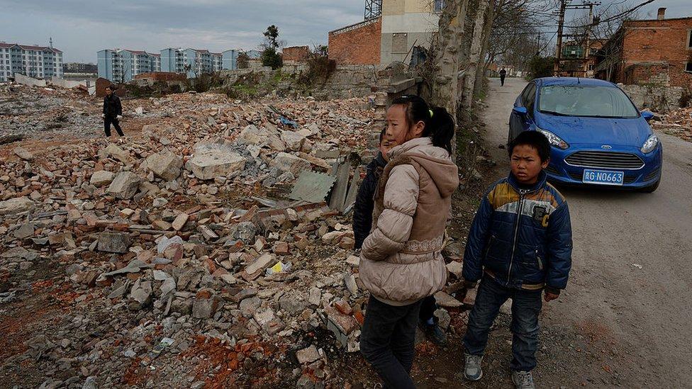 Unos niños observan las construcciones a lo lejos de nuevos edificios en Anshun, provincia de Guizhou, 2014