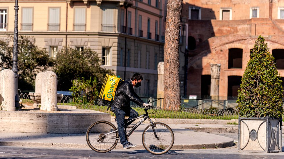 A food delivery man rides his bicycle in Rome
