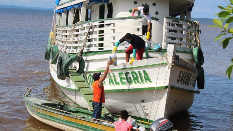 Tripulação de barco transfere kits de limpeza e alimento para embarcação menor