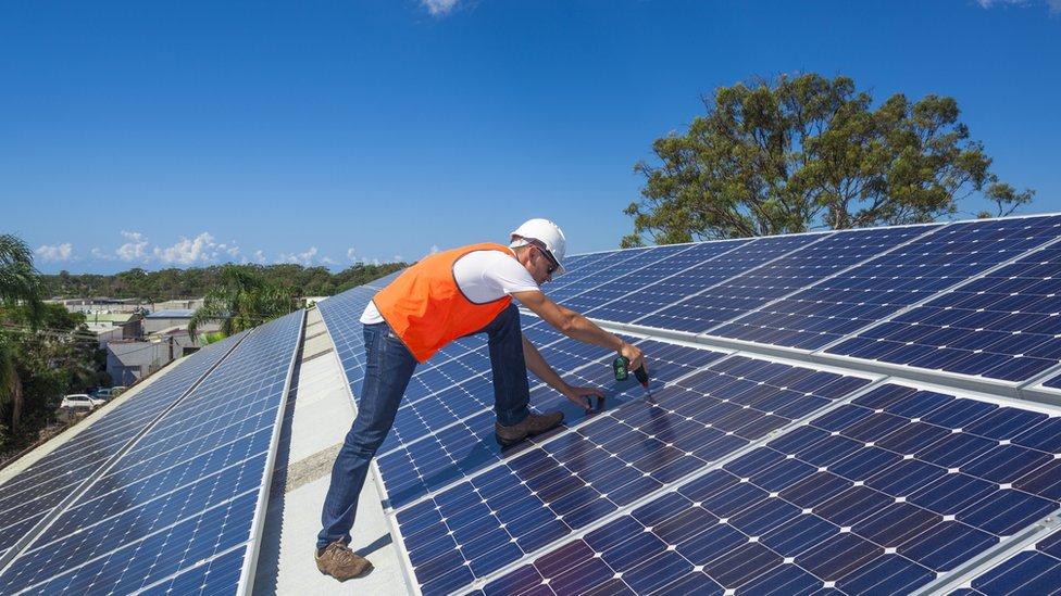 Hombre sobre tejado repleto de paneles solares.