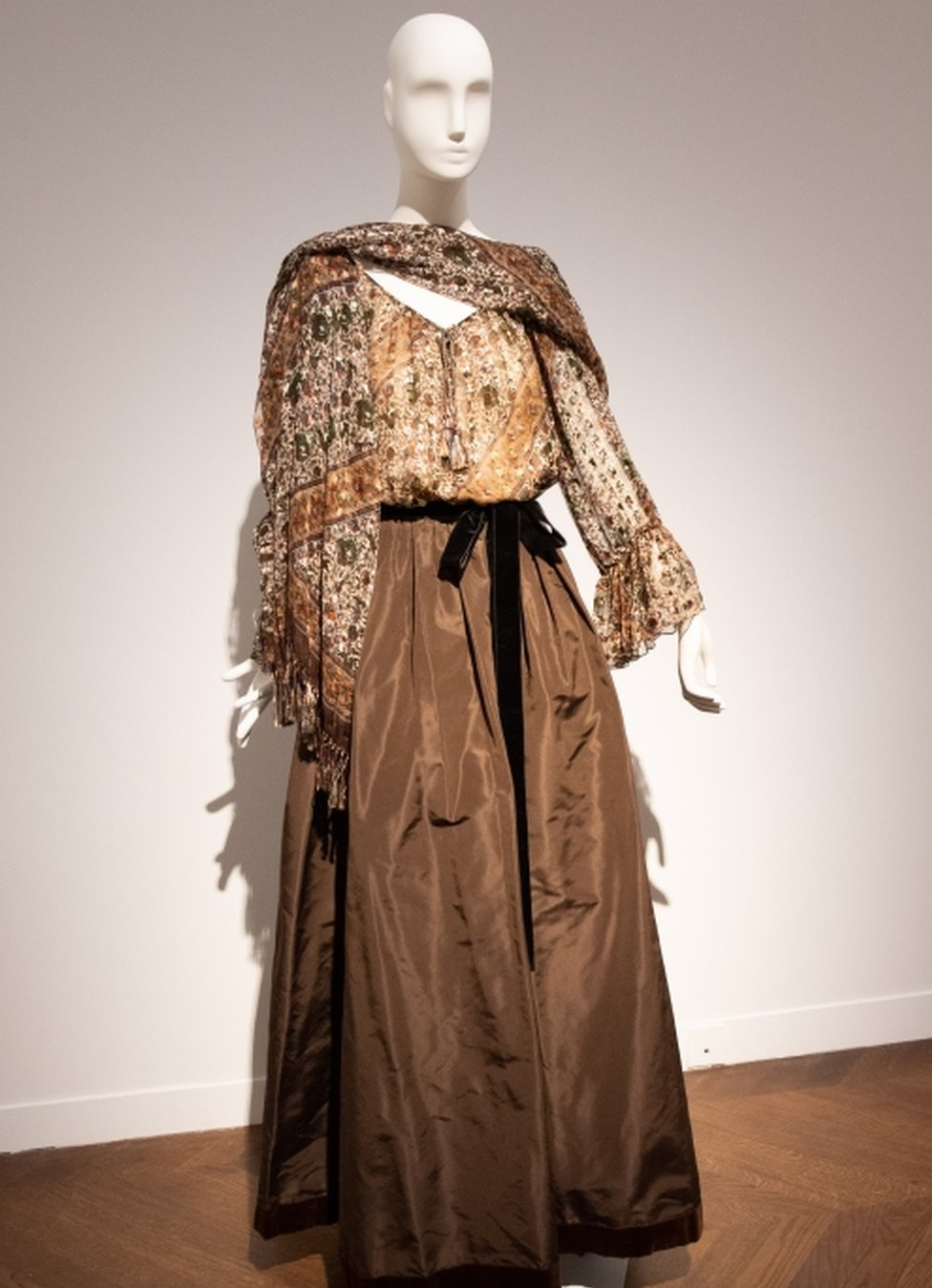 A long brown evening gown featuring a ribbon at the waist, and a wrap shawl