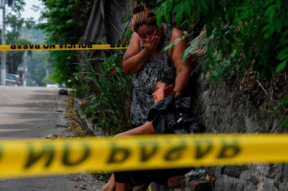 Familiares de un hombre asesinado en Ayutuxtepeque, El Salvador, lloran junto a la escena del crimen el 28 de abril de 2020.